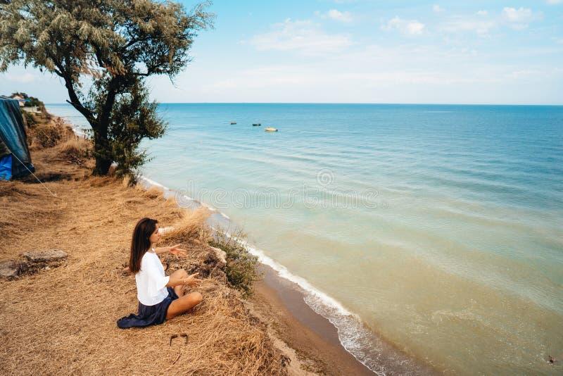 Attraktive Frau im Sommerrock und -hemd sitzt auf dem Ufer lizenzfreie stockbilder