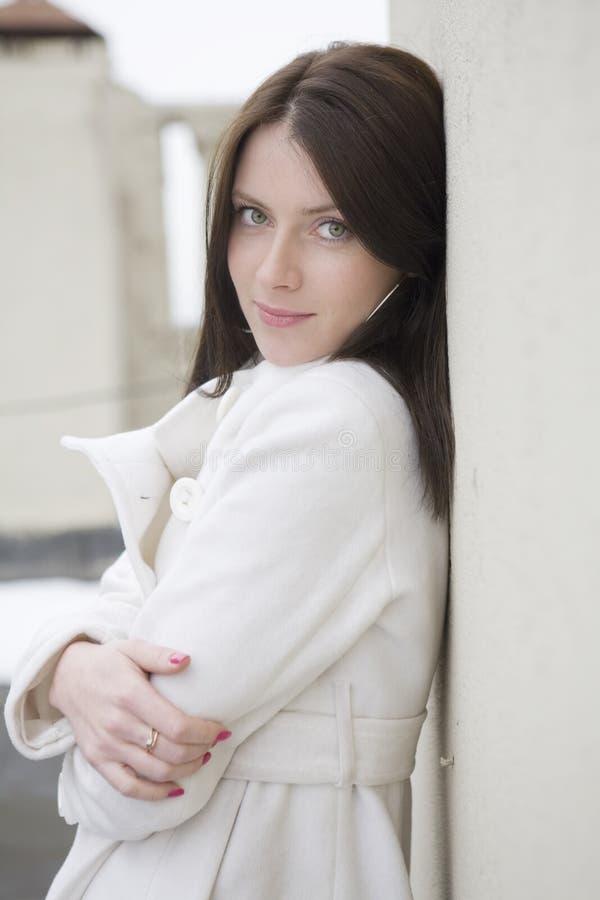 Attraktive Frau im weißen Oberen an der Wand lizenzfreie stockfotos
