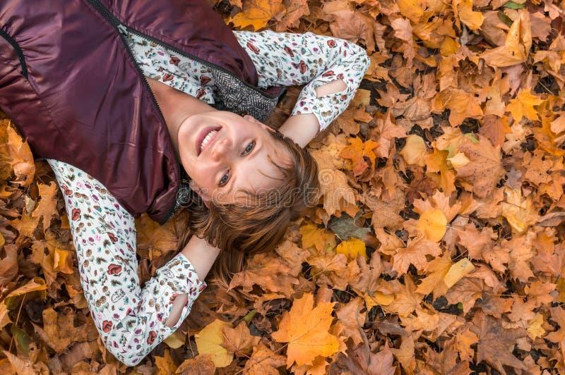 Attraktive Frau liegt über Herbstlaub im Park stockfotografie