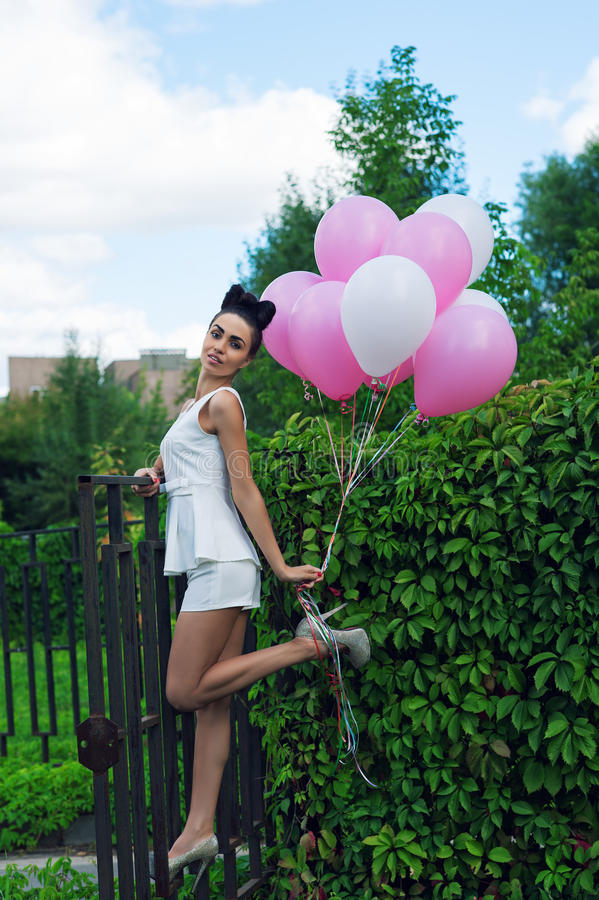 Attraktive Frau mit Ballonen auf den Eisentoren lizenzfreie stockfotos
