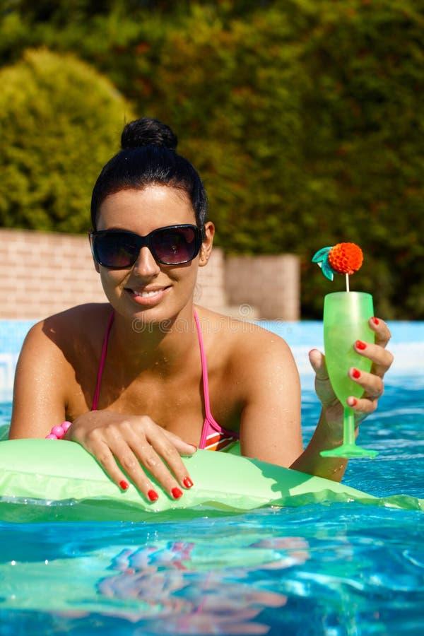 Attraktive Frau mit Cocktail im Swimmingpool lizenzfreies stockfoto