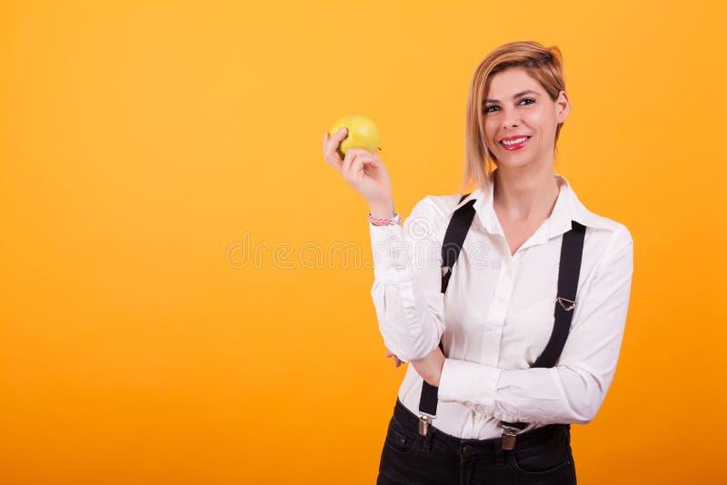 Attraktive Frau mit dem blonden Haar, das Arme gekreuzt hält und einen grünen Apfel über gelbem Hintergrund hält stockfoto