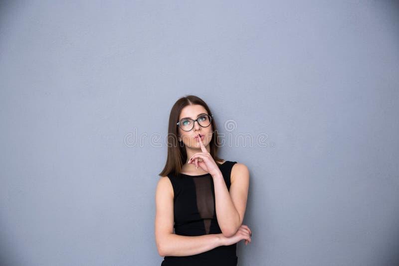 Attraktive Frau mit dem Finger über den Lippen, die oben copyspace betrachten lizenzfreies stockbild