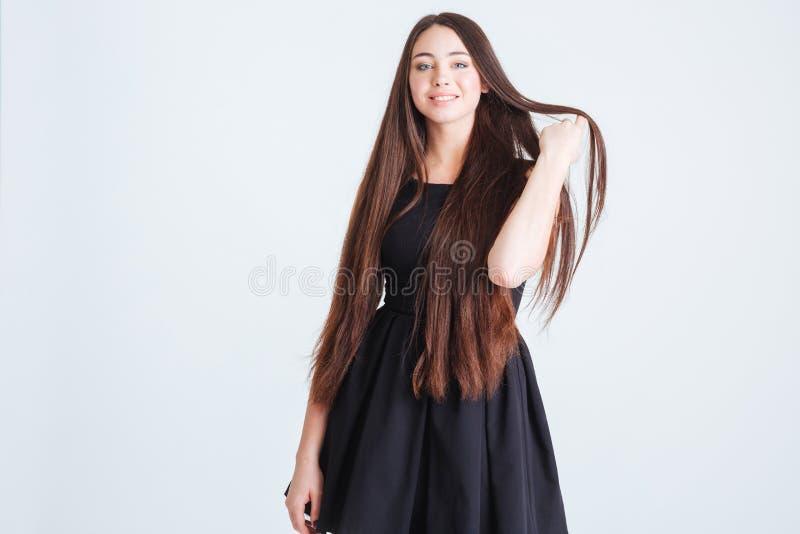Attraktive Frau mit dem schönen langen dunklen Haar im schwarzen Kleid lizenzfreie stockfotografie