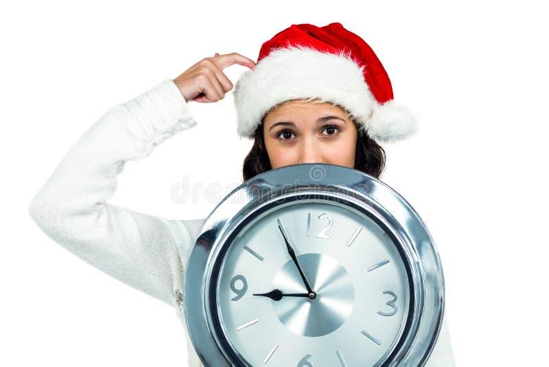 Attraktive Frau mit dem Weihnachtshut, der Uhr hält stockfoto