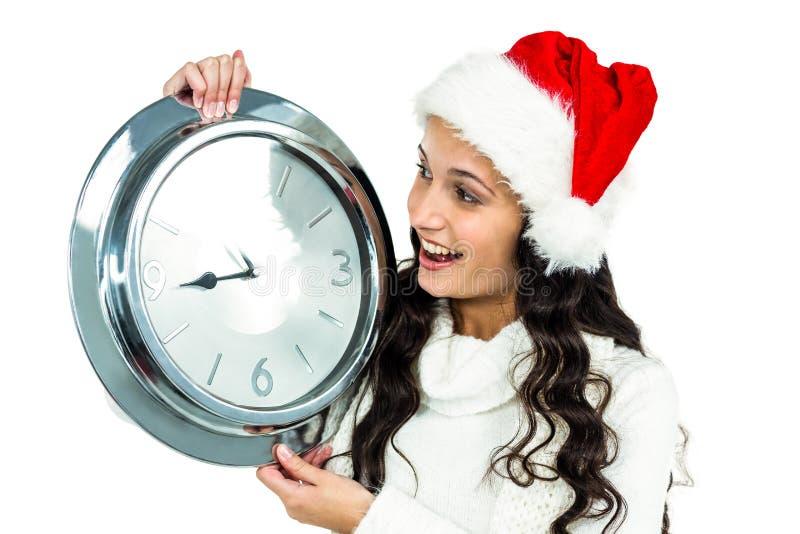 Attraktive Frau mit dem Weihnachtshut, der Uhr hält lizenzfreie stockfotos