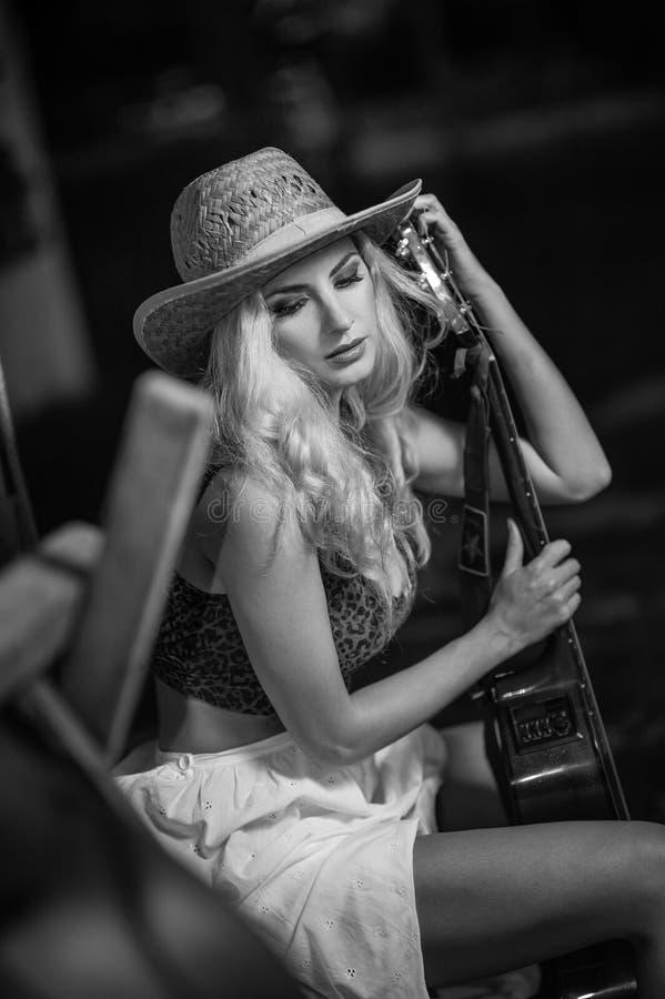 Attraktive Frau mit Landblick, schoss zuhause, amerikanischer Landhausstil Mädchen mit StrohCowboyhut und Gitarre Schöne Blondine stockfotos