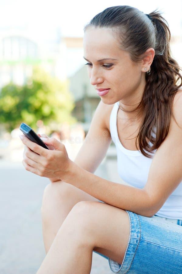 Attraktive Frau mit Mobiltelefon stockbild