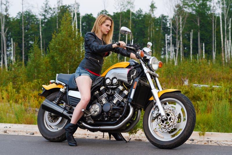 Attraktive Frau mit Motorrad draußen stockbild