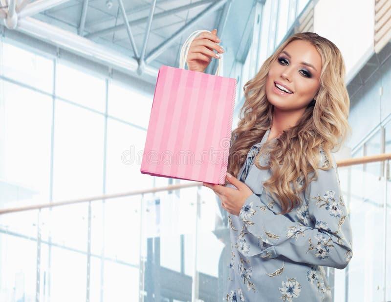 Attraktive Frau mit rosa Einkaufstaschen auf Geschäftshintergrund lizenzfreies stockfoto