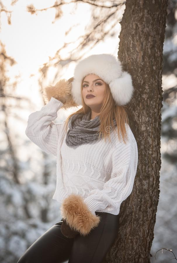 Attraktive Frau mit weißer Pelzmütze und Jacke den Winter genießend Seitenansicht der modernen blonden Mädchenaufstellung lizenzfreies stockfoto