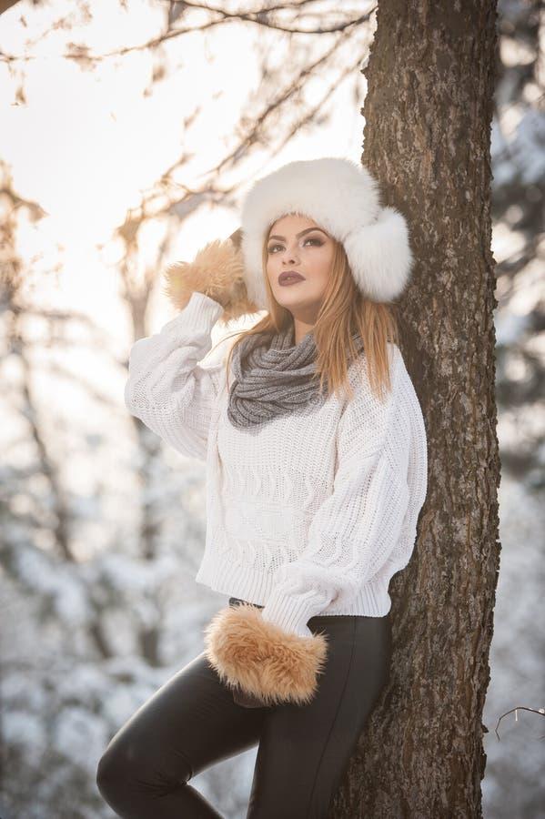 Attraktive Frau mit weißer Pelzmütze und Jacke den Winter genießend Seitenansicht der modernen blonden Mädchenaufstellung lizenzfreie stockfotos