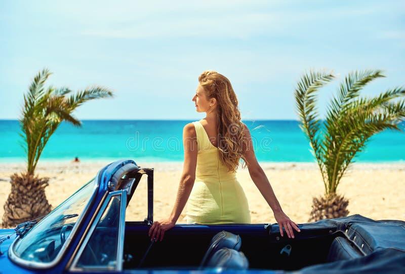 Attraktive Frau nahe Retro- Auto auf dem tropischen Strand lizenzfreies stockfoto