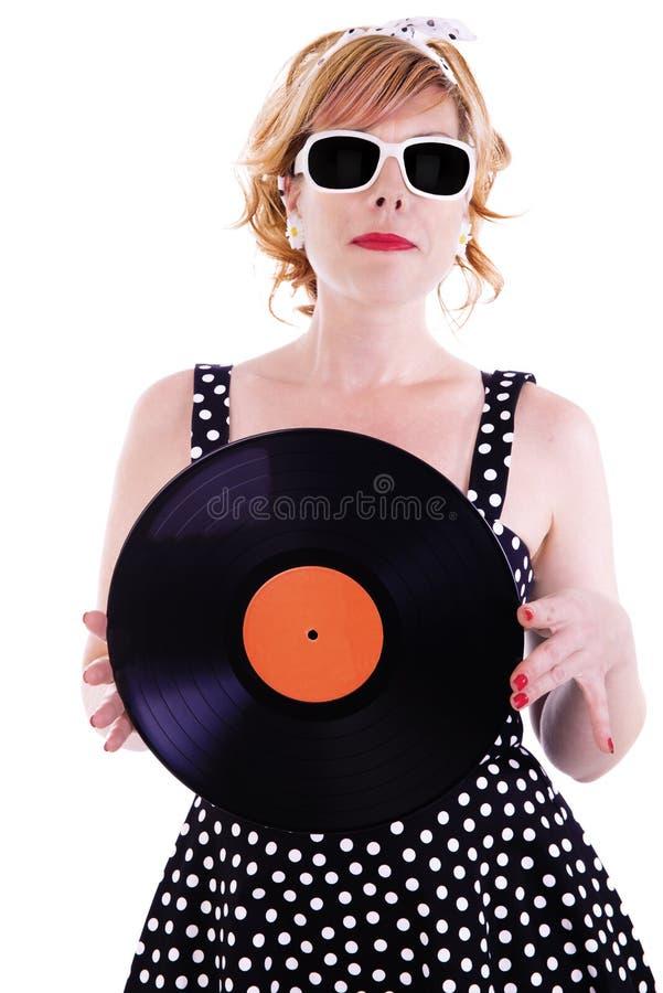 Attraktive Frau sieht wie ein Pinup aus und hält eine Vinylaufzeichnung in ihren Händen stockbild