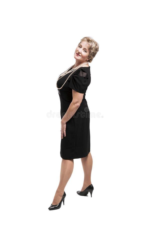Attraktive Frau von mittlerem Alter im schwarzen Kleid stockbild
