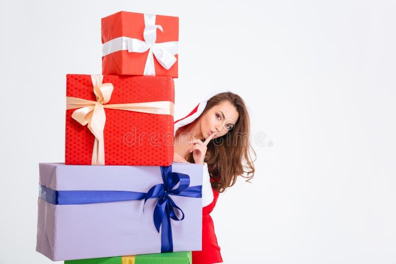 Attraktive Frau in Weihnachtsmann-Kostüm, das hinter Präsentkartons sich versteckt stockbild