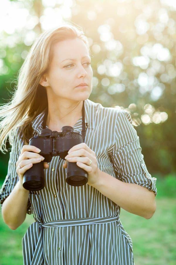 Attraktive Frau, welche die Ferngläser im Freien in der Natur hat stockfoto