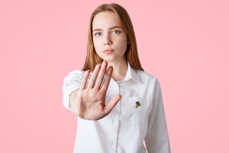Attraktive Frau zeigt Verbotgeste, ausdehnt Hand, Fokus auf Palme, ablehnt, in Restaurant mit den Freunden zu gehen, gekleidet in stockbild
