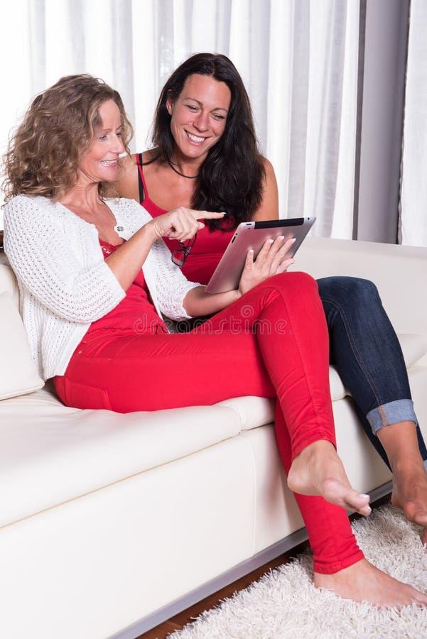 Attraktive Frau zwei, die auf der Couch lacht über was sie s siiting ist lizenzfreies stockfoto