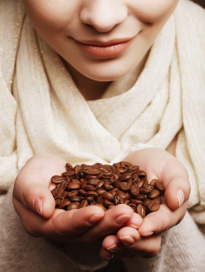 Attraktive Frauenholding-Kaffeebohnen lizenzfreie stockfotos