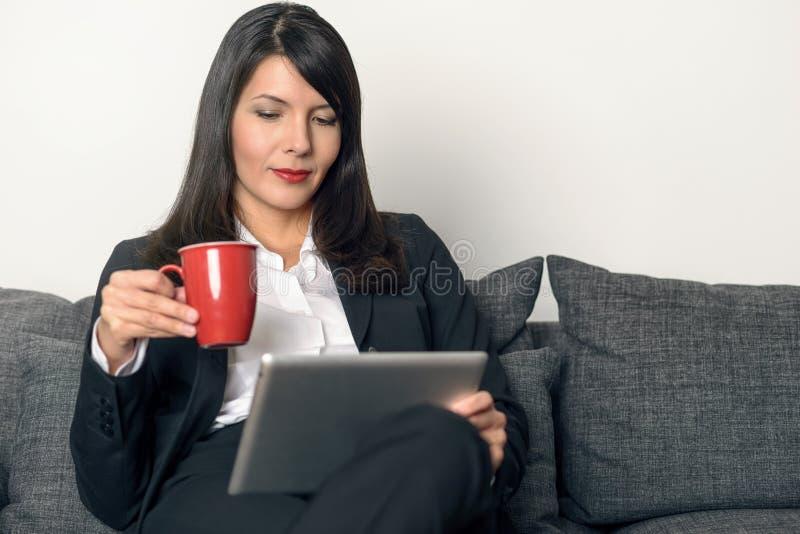 Attraktive Frauenlesung auf einem Tabletten-PC stockfoto