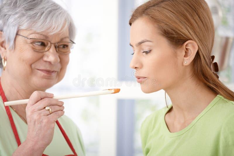Attraktive Frauenprobierennahrung beim Kochen lizenzfreies stockfoto