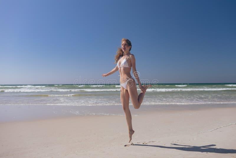 Attraktive Frauenstellung auf Spitzenzehe am Strand lizenzfreie stockfotos