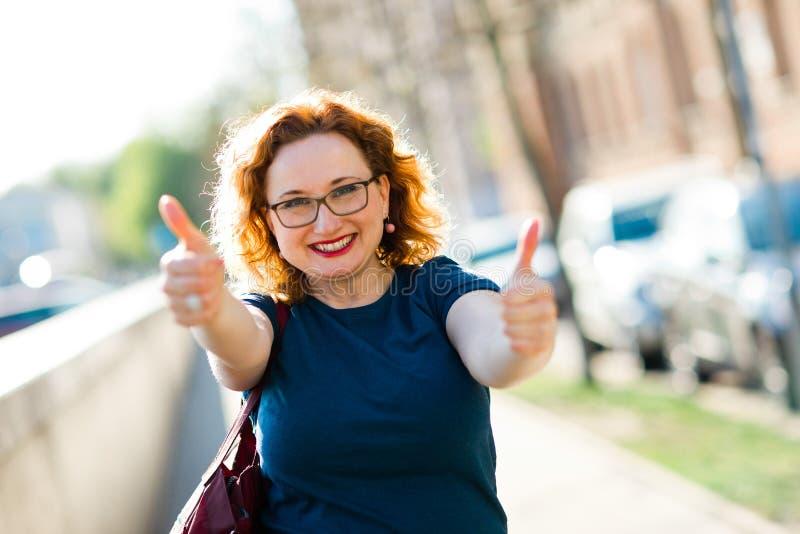 Attraktive Frauenvertretungsgeste mit den Fingern - Daumen oben lizenzfreies stockbild