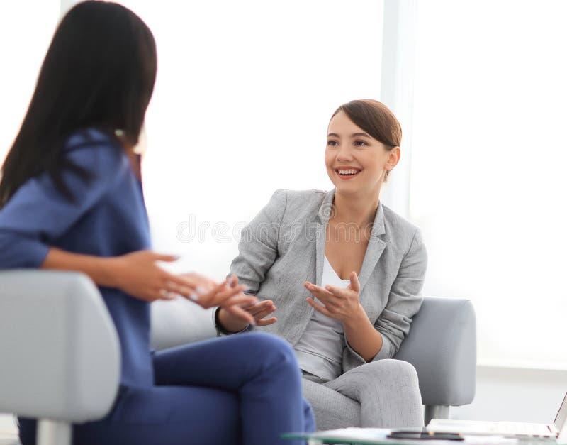Attraktive Freundinnen, die während einer Büropause plaudern lizenzfreies stockfoto