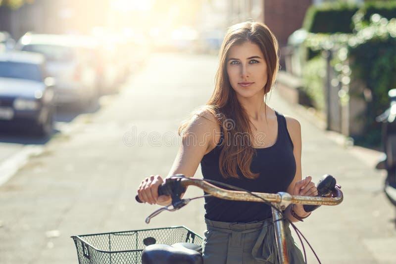 Attraktive freundliche junge Frau oder Student mit ihrer Fahrradstellung in einer städtischen Straße im Sommersonnenschein glückl stockbilder