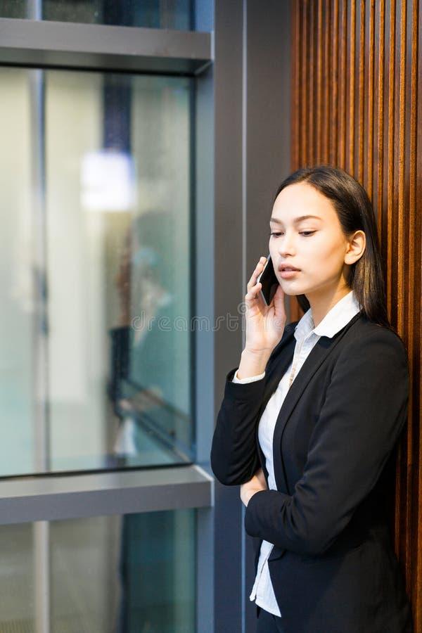 Attraktive Geschäftsfrau Answering beim Telefon-Anruf lizenzfreie stockfotografie