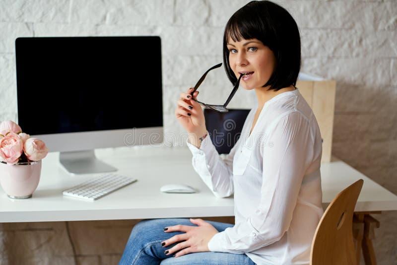 Attraktive Geschäftsfrau, die an Computer an ihrem Arbeitsplatz mit weißem Schreibtisch arbeitet stockfotografie