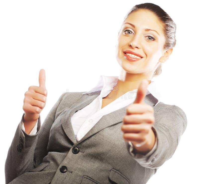 Attraktive Geschäftsfrau, die Daumen aufgibt stockbild