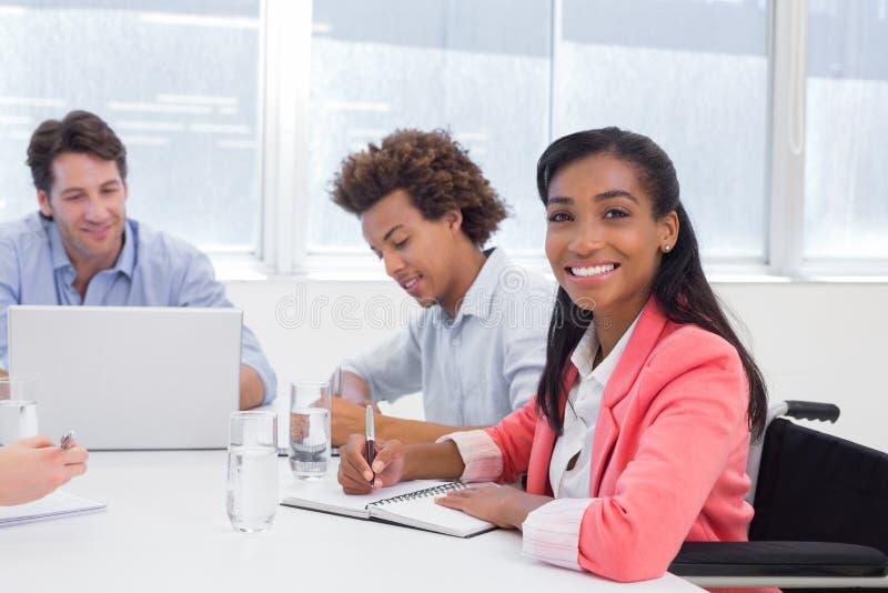 Attraktive Geschäftsfrau, die an dem Arbeitsplatz lächelt stockfotografie