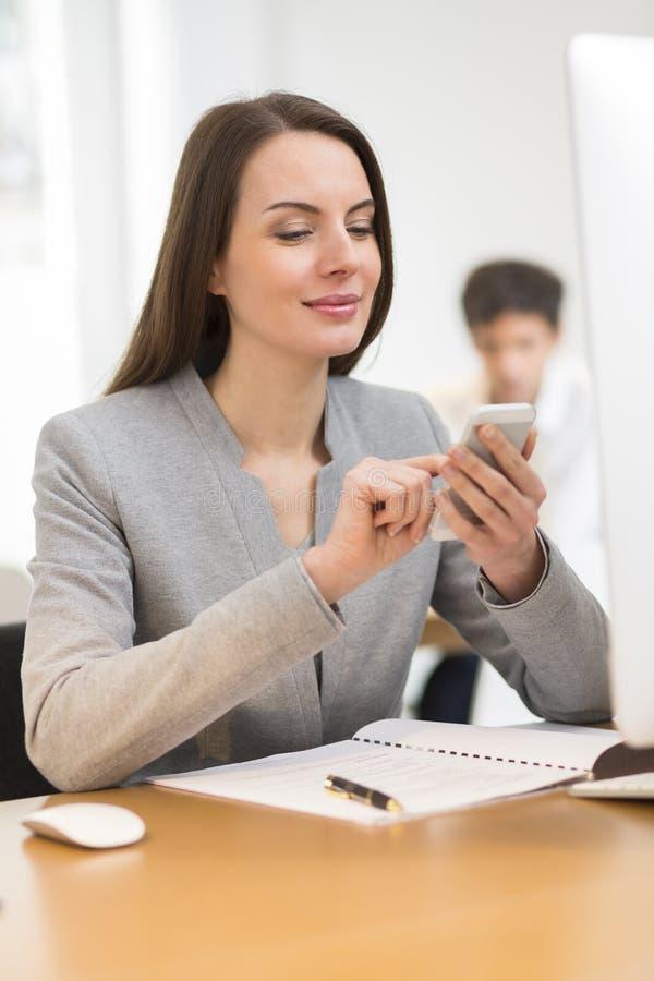 Attraktive Geschäftsfrau, die Handy im Büro verwendet stockbild