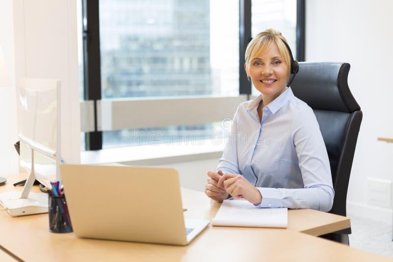 Attraktive Geschäftsfrau, die an Laptop arbeitet kopfhörer Gebäude b lizenzfreies stockfoto