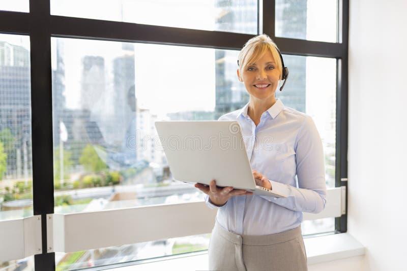 Attraktive Geschäftsfrau, die an Laptop arbeitet kopfhörer Gebäude b stockfotografie