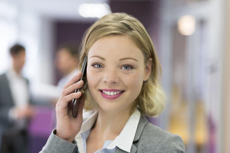 Attraktive Geschäftsfrau, die mit Handy in modernem weg nennt lizenzfreies stockbild