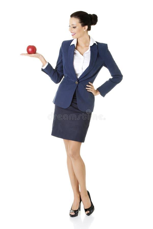 Attraktive Geschäftsfrau, die roten Apfel anhält stockfotos