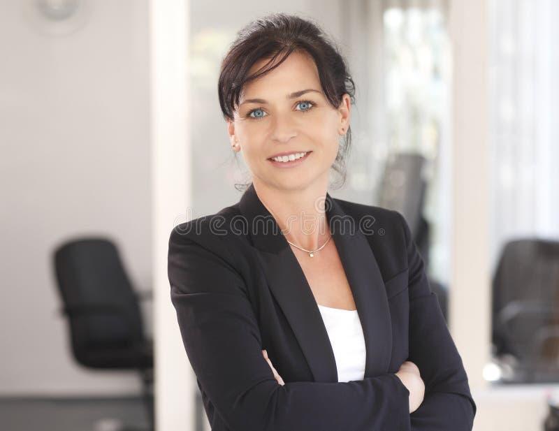 Attraktive Geschäftsfrau mit ihren Armen gekreuzt stockfotografie