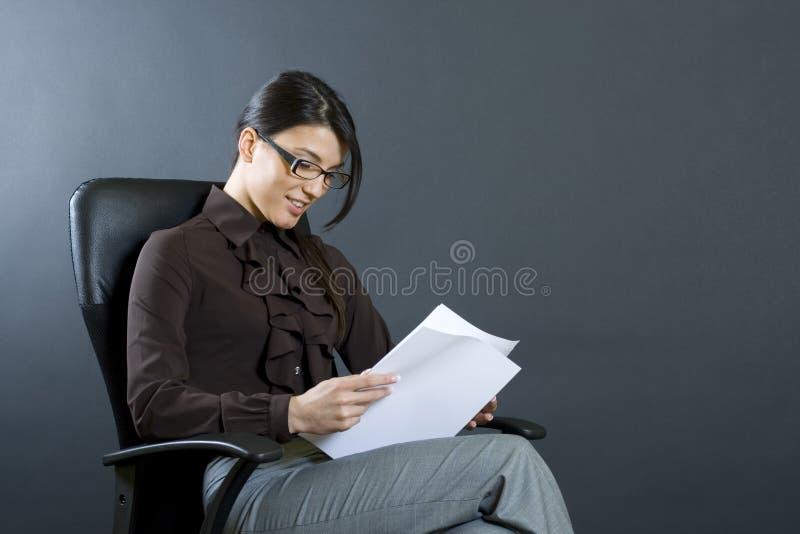 Attraktive Geschäftsfraulesepapiere lizenzfreies stockfoto