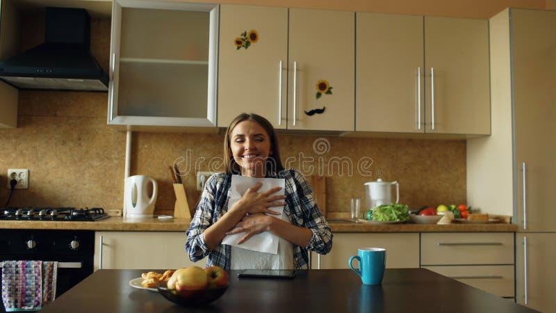 Attraktive glückliche Frau erhalten Brief der guten Nachrichten Lesein der Küche, während frühen Morgen des Frühstücks zu Hause h stockbild