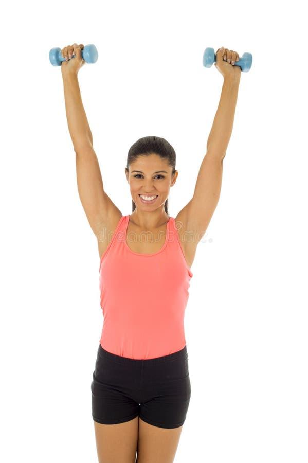 Attraktive glückliche lateinische Frau, die den Gewichtsdummkopf tut Eignungstraining hält stockbilder