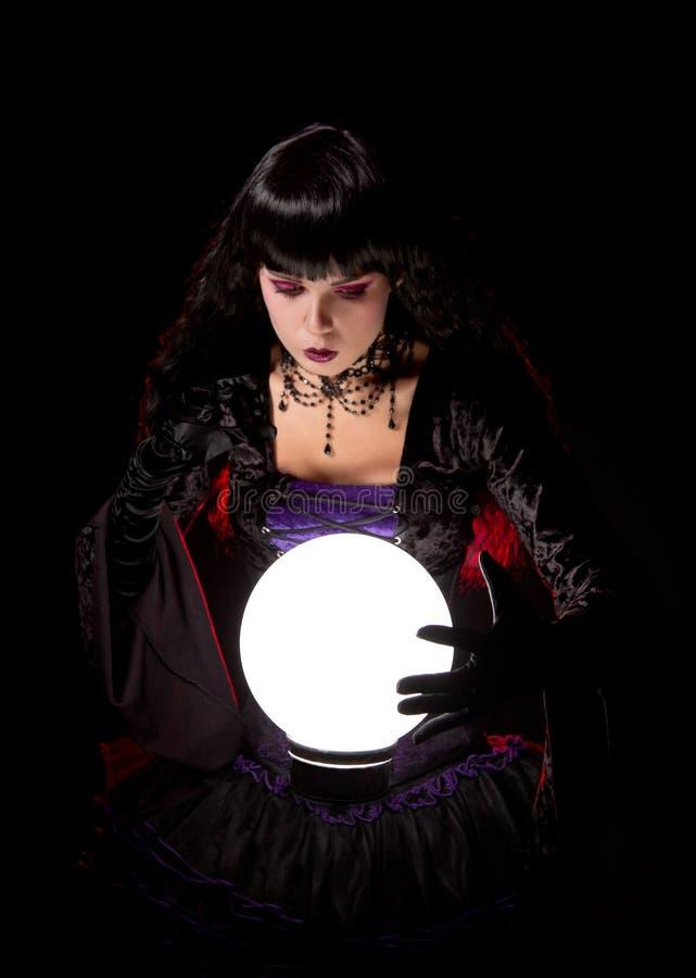 Attraktive Hexe oder Wahrsager, die eine Glaskugel untersuchen stockbilder