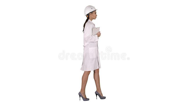 Attraktive hispanische Frau im weißen Laborkittel und im weißen Sicherheitsschutzhelm gehend, Notizbuch oder Tablette auf Weiß ha stockfotos