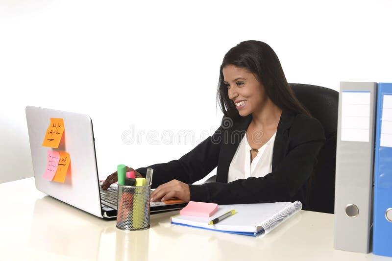 Attraktive hispanische Geschäftsfrau, die am Schreibtisch arbeitet auf dem Computerlaptoplächeln glücklich sitzt lizenzfreies stockbild