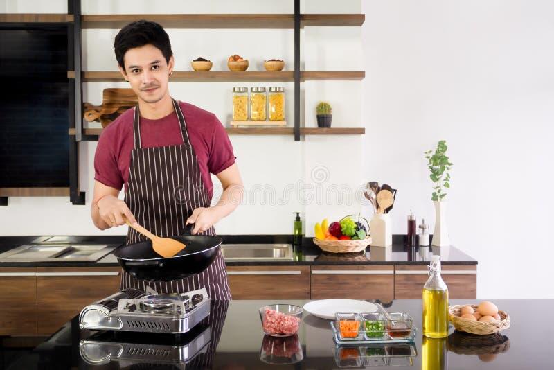 Attraktive Holdingwanne des jungen Mannes und hölzerne Spachtel, zum des Omeletts zum Frühstück an der modernen Küche morgens lizenzfreie stockfotografie