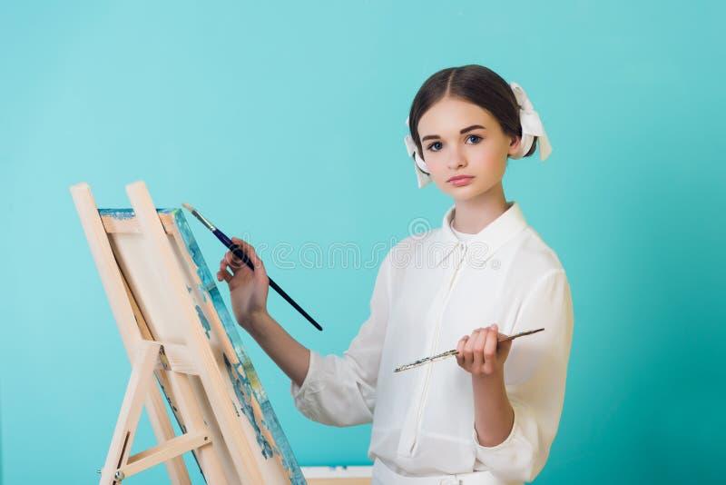 attraktive jugendlich Mädchenmalerei auf Gestell mit Bürste und Palette stockbilder