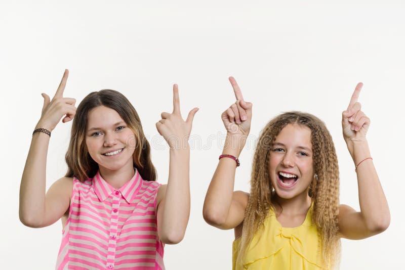 Attraktive Jugendliche des Positivs zwei, die oben ihren Zeigefinger zeigt lizenzfreies stockbild