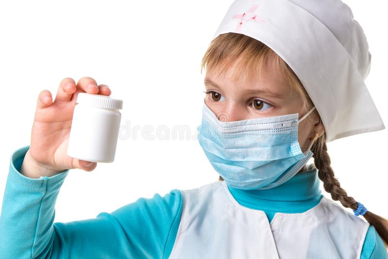 Attraktive junge Ärztin, die auf das weiße Tablettenfläschchen lokalisiert auf weißem Hintergrund zeigt stockfoto